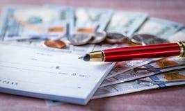 Livro de verificação, pena vermelha, cem notas de dólar, moedas Economia da finança e conceito do investimento U S Notas de banco fotografia de stock royalty free