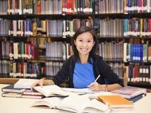 Livro do assento e de leitura do estudante na biblioteca Imagem de Stock Royalty Free