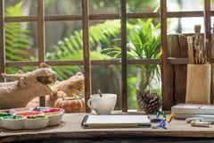 Livro do esboço na mesa do trabalho do artista no jardim pequeno Fotos de Stock Royalty Free