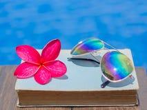 Livro e óculos de sol, fundo da água azul, Foto de Stock Royalty Free