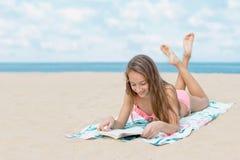 Livro e banho de sol bonitos de leitura da menina do adolescente na praia no dia de verão quente com o mar e no horizonte no fund Fotos de Stock Royalty Free