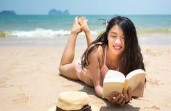 Livro e banho de sol de leitura da menina na praia Fotografia de Stock
