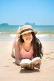Livro e banho de sol de leitura da menina na praia Foto de Stock