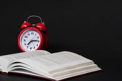 Livro e despertador no fundo preto fotos de stock