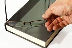 Livro e eyeglasses disponivéis imagem de stock