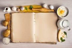 Livro e ingredientes do cozinheiro do vintage para a receita do alimento ao redor dentro Imagem de Stock
