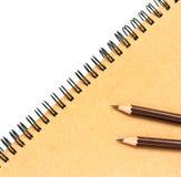 Livro e lápis de nota do papel de embalagem no branco Foto de Stock Royalty Free