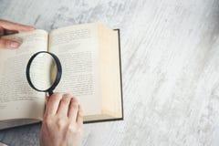 Livro e lente de aumento da mão da mulher fotos de stock