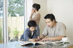 Livro e mulher de And Son Coloring do pai na chamada em casa imagens de stock