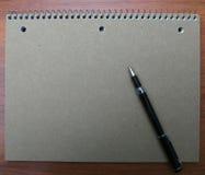 Livro e pena de nota na mesa Imagens de Stock Royalty Free