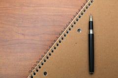 Livro e pena de nota na mesa Fotografia de Stock