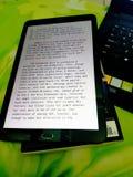 Livro e portátil da tabuleta ao trabalhar imagem de stock royalty free