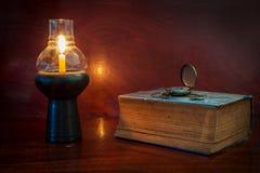 Livro e relógio antigos com lâmpada Fotografia de Stock Royalty Free