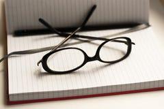 Livro e vidros de nota da pena no branco fotografia de stock