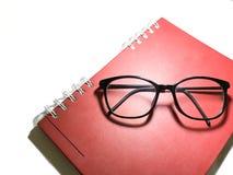 Livro e vidros vermelhos Imagem de Stock