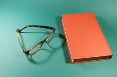 Livro e vidros vermelhos Fotos de Stock Royalty Free