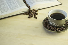Livro e xícara de café na tabela de madeira Imagem de Stock Royalty Free