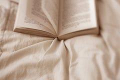 Livro em uma cama Imagens de Stock Royalty Free