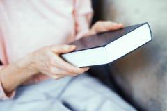 Livro grosso azul nas mãos de uma mulher idosa imagem de stock royalty free