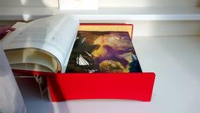 Livro grosso grande coberto com um pano vermelho com uma gravura na parte dianteira de filme