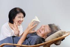 Livro idoso da fábula da leitura da mulher com filha Imagem de Stock