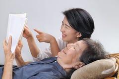 Livro idoso da fábula da leitura da mulher com filha Foto de Stock Royalty Free