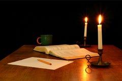 Livro, lápis e papel iluminados pela luz de vela Imagens de Stock