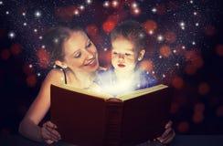 Livro mágico da leitura da filha do bebê da mãe e da criança na obscuridade Imagem de Stock