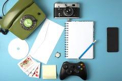 Livro, pulso de disparo, câmera, telefone, jogo, caderno, CD, lápis combinado em um telefone celular Conceito em um fundo da cor fotos de stock royalty free
