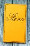 Livro quadro amarelo do menu na madeira Imagens de Stock