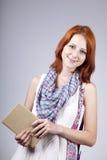 Livro Red-haired do sustento da menina à disposicão. fotos de stock