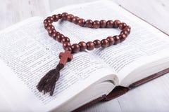 Livro sagrado e cruz religiosos do tema em um fundo de madeira branco Fotos de Stock Royalty Free