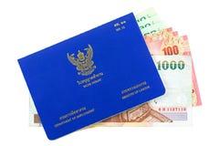 Livro tailandês azul da autorização de trabalho com baht tailandês diferente dentro do isola foto de stock