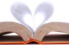 Livro velho com folhas que formam uma forma do coração fotografia de stock