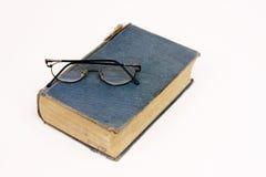 Livro velho com os vidros de leitura que descansam no branco Fotografia de Stock Royalty Free