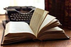 Livro velho do vintage com luminoso e e a máquina de escrever velha no conceito da literatura da bibliografia do fundo foto de stock