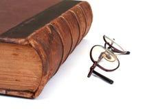Livro velho e eyeglasses Foto de Stock