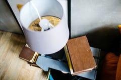 Livro velho e lâmpada branca na tabela de cabeceira fotos de stock royalty free