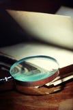 Livro velho e magnifier imagens de stock royalty free