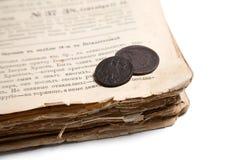 Livro velho e moedas Fotografia de Stock