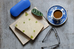 Livro velho, vidros, xícara de café e um envelope na tabela Do vintage vida ainda Imagens de Stock