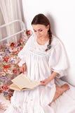 Livro vermelho da mulher em uma cama Fotografia de Stock