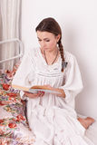 Livro vermelho da mulher em uma cama Fotos de Stock Royalty Free