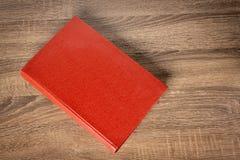 Livro vermelho na tabela Fotografia de Stock Royalty Free