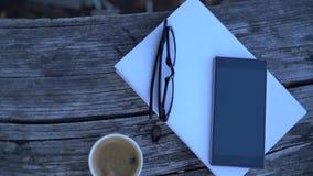 Livro, vidros, telefone celular e café filme