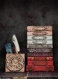 Livros antigos, manuscritos e um tinteiro antigo em uma prateleira e decoração do estuque do emplastro da gipsita foto de stock royalty free