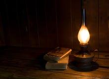 Livros antigos velhos com a lâmpada ardente da parafina Fotografia de Stock