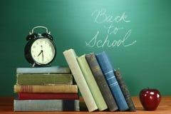 Livros, Apple e pulso de disparo de escola na mesa na escola Fotos de Stock