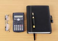 Livros da pena e do negócio de fonte e calculadora e monóculos sobre fotografia de stock