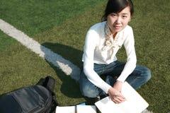 Livros da terra arrendada da menina que sentam-se em grasslan Fotos de Stock Royalty Free